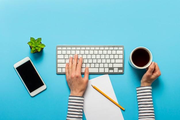 Vrouw werkt op kantoor op een blauwe. conceptenwerkruimte, werken op een computer, freelance Premium Foto