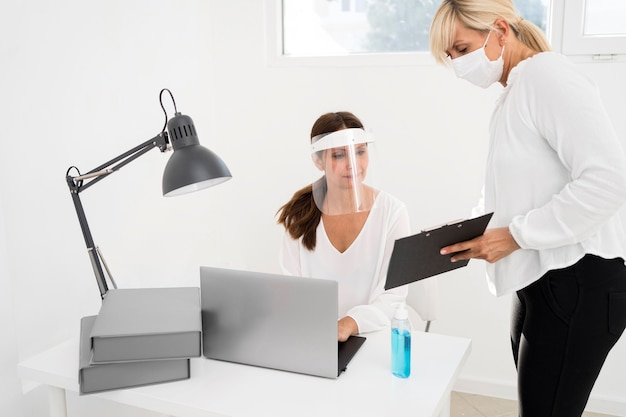 Vrouw werkt samen en draagt gezichtsbescherming Gratis Foto