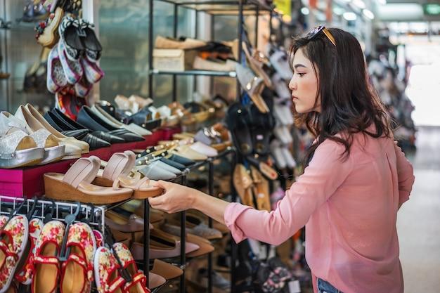 Vrouw winkelen schoenen in een winkel Premium Foto