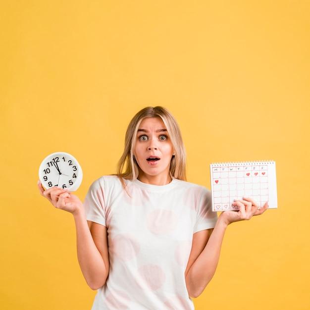 Vrouw wordt verrast en houdt een klok en een menstruele kalender vast Gratis Foto