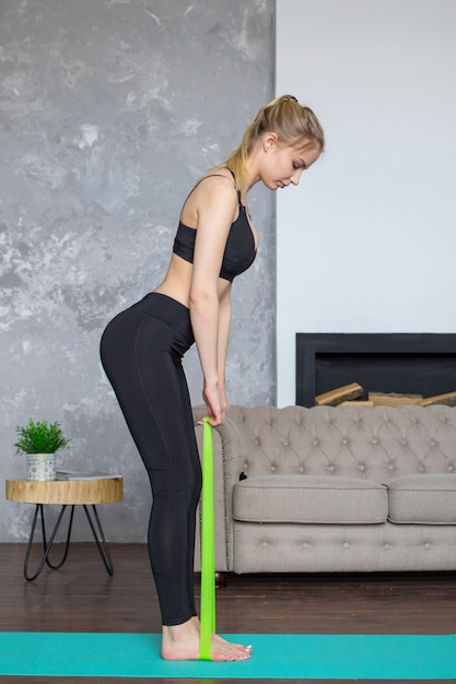 Vrouw workouts thuis met fitness tandvlees, training thuis Premium Foto