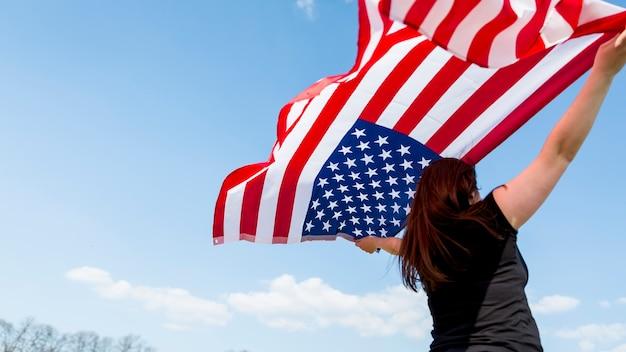 Vrouw wuivende vlag van de verenigde staten tijdens de viering van de dag van de onafhankelijkheid Gratis Foto