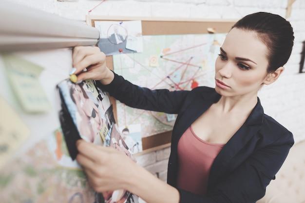 Vrouw zet foto's op clue map in office. Premium Foto