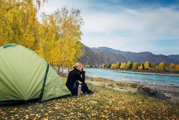 Vrouw zit in de buurt van toeristische tent en drinkt hete thee Premium Foto