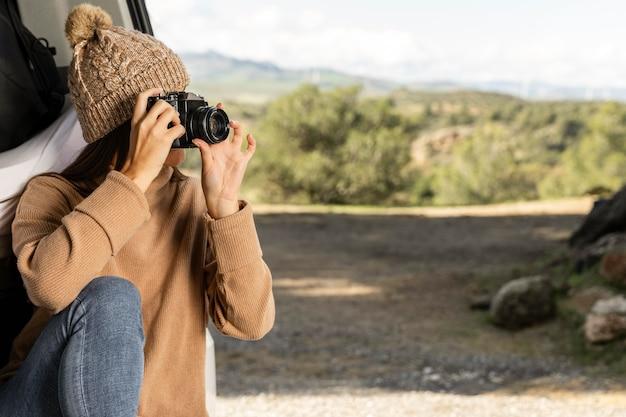 Vrouw zit in de kofferbak van de auto tijdens een roadtrip en houdt de camera vast Premium Foto