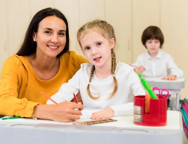 Vrouw zit naast haar student Gratis Foto