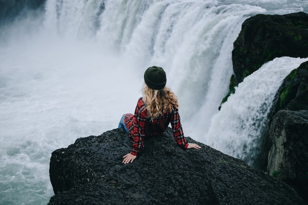 Vrouw zit op de rand van de klif op de waterval Gratis Foto