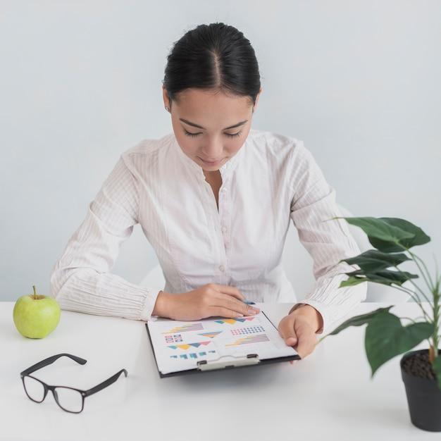 Vrouw zit op haar werkplek Gratis Foto