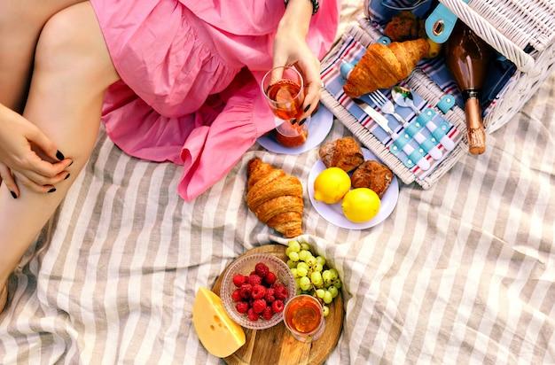 Vrouw zitten en houden glas champagne, traditioneel fruit, croissants en kaas, Gratis Foto