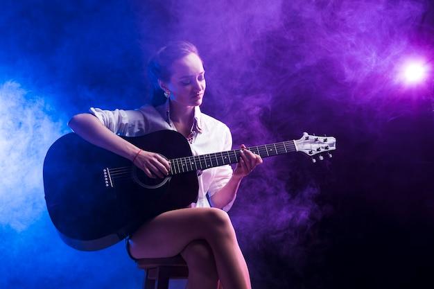 Vrouw zitten in de klassieke positie voor het spelen van de gitaar Gratis Foto