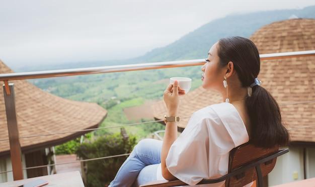 Vrouw zitten in een terrca genieten van aziatische landschap Premium Foto