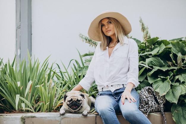Vrouw zitten in park met haar pug-hond huisdier Gratis Foto