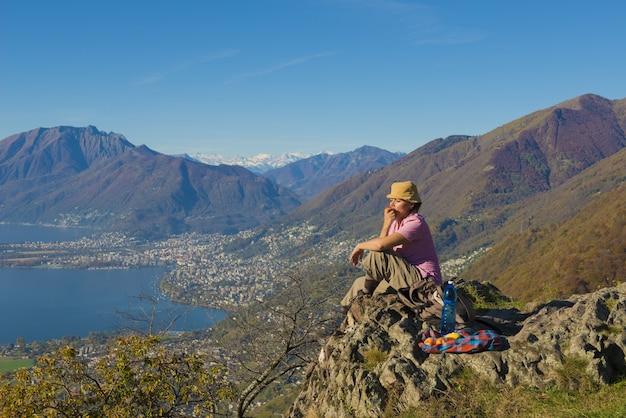 Vrouw zittend op de rots met een prachtig uitzicht op de bergen in de buurt van de kust Gratis Foto