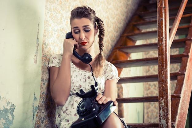 Vrouw zittend op de trap en huilen aan de telefoon Premium Foto