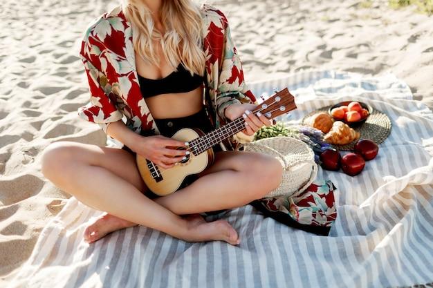 Vrouw zittend op dekking op het strand in zachte kleuren van de zonsondergang en ukelele gitaar spelen. vers fruit, croissants en perzik op de plaat. Gratis Foto