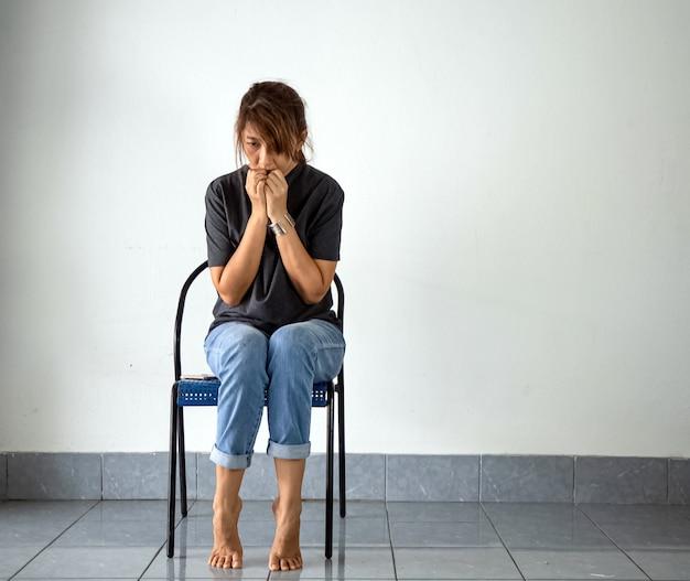 Vrouw zittend op een stoel, met stress en boos gevoel. heb mentale problemen Premium Foto