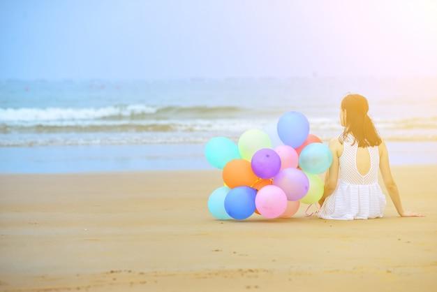 Bekend Vrouw, zittend op het zand naast een bos van ballonnen Foto  QW23