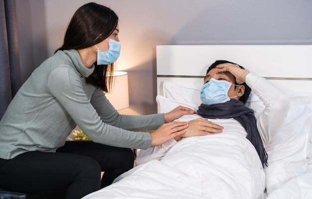 Vrouw zorgt thuis voor haar zieke man op bed, mensen moeten een medisch masker dragen dat beschermt tegen een pandemie van het coronavirus Premium Foto