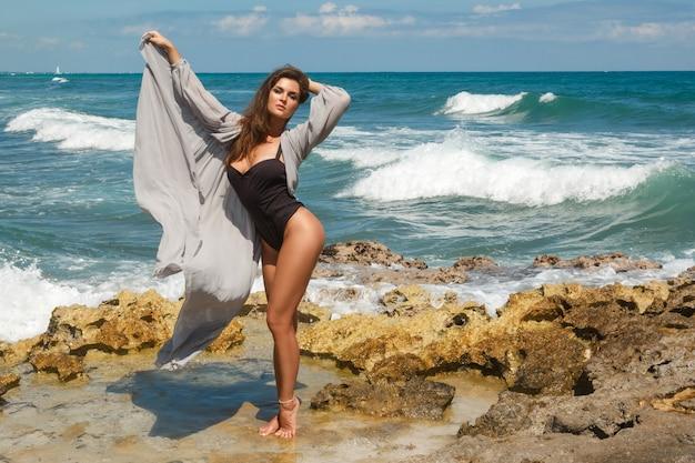 Vrouw zwarte bodysuit en mooie zijden jurk dragen op het strand met rotsen Premium Foto