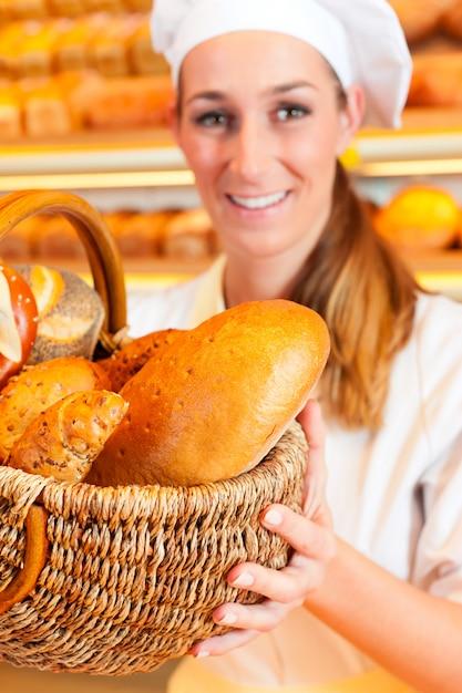 Vrouwelijk bakkers verkopend brood door mand in bakkerij Premium Foto