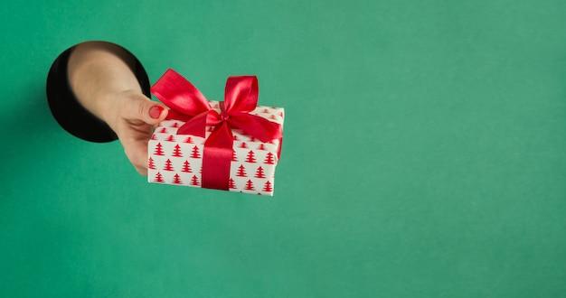 Vrouwelijk de giftvakje van de handholding door rond gat in groenboek. Premium Foto