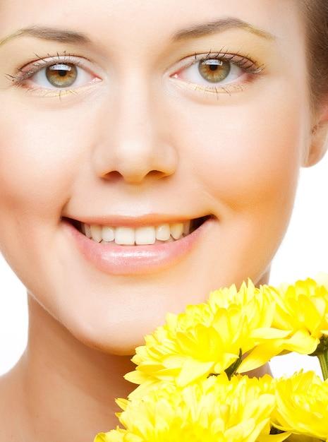 Vrouwelijk gezicht met de gele chrysant Premium Foto