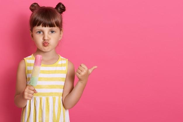 Vrouwelijk jong geitje die roomijs houden en opzij met duim richten, geïsoleerd stellen over roze muur, lippen rond houdend, ziet het kleine meisje zakelijk en grappig. Gratis Foto