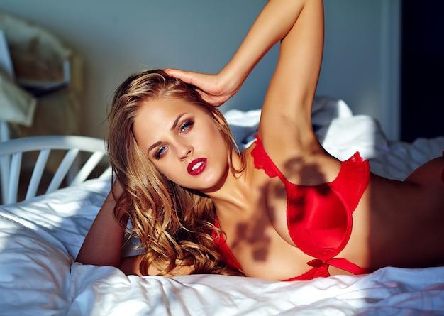 Vrouwelijk model die rode erotische lingerie op bed in de ochtend dragen Gratis Foto