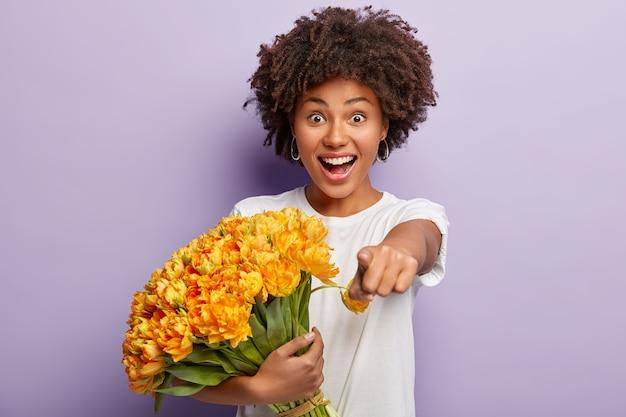 Vrouwelijk model heeft een afro-kapsel, dolgelaatsuitdrukking, wijst rechtstreeks naar de camera, geeft uitdrukking aan keuze Gratis Foto