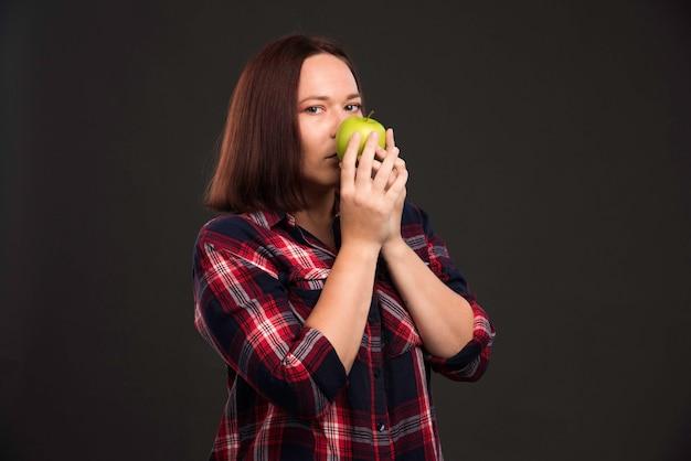 Vrouwelijk model in herfst-wintercollectie-outfits die een groene appel vasthouden en eraan ruiken. Gratis Foto