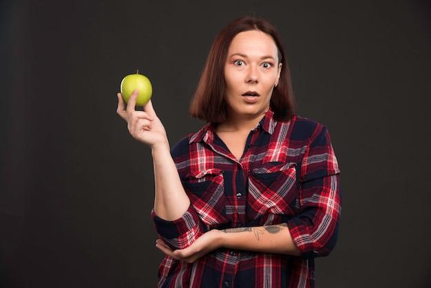 Vrouwelijk model in herfst-wintercollectie-outfits die een groene appel vasthouden en zich verrast voelen. Gratis Foto