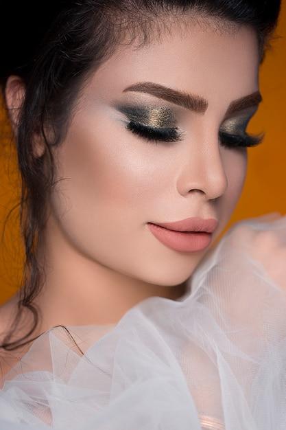 Vrouwelijk model in smokey eyes make-up en het dragen van roze lippenstift Gratis Foto