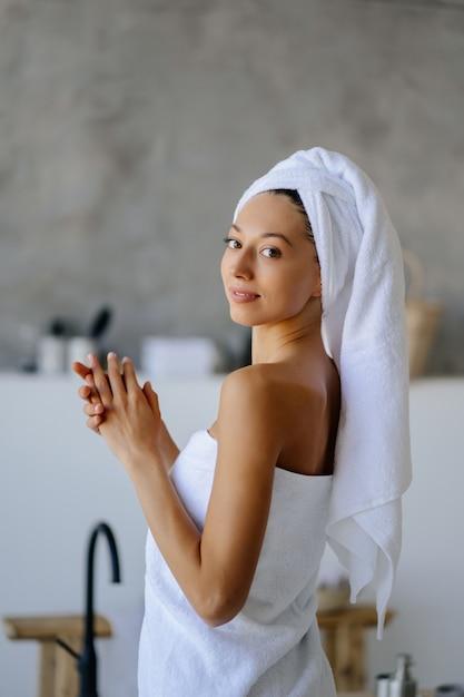 Vrouwelijk model in witte handdoek. vrouwen, schoonheid en hygiëne concept. Gratis Foto