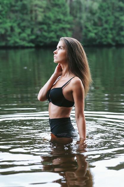 Vrouwelijk model in zwarte zwembroek in het meer Gratis Foto