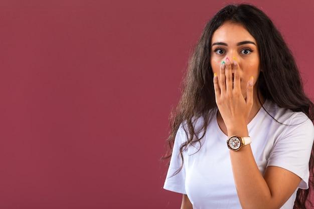 Vrouwelijk model maakt verbaasd gezicht, vooraanzicht op roze muur. Gratis Foto
