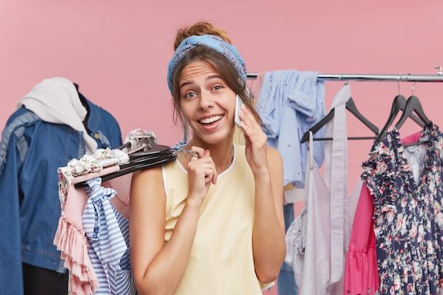Vrouwelijk model pronkt met haar nieuwe aankopen, belt haar beste vriendin terwijl ze hangers vasthoudt met kleren in het warenhuis of in de paskamer. positieve vrouw die op celtelefoon babbelt en het winkelen doet Gratis Foto