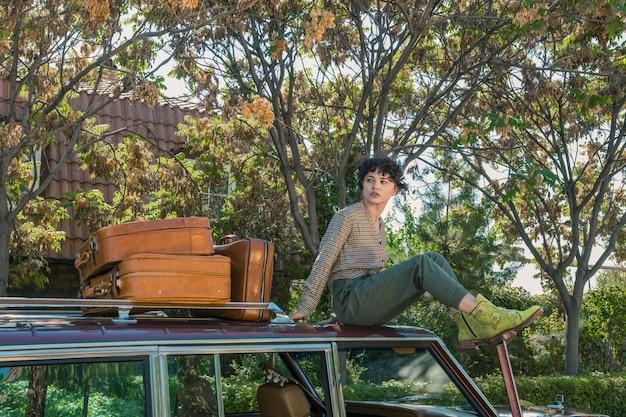 Vrouwelijk model zittend op een auto poseren voor een fotoshoot met suticases aan de zijkant Gratis Foto