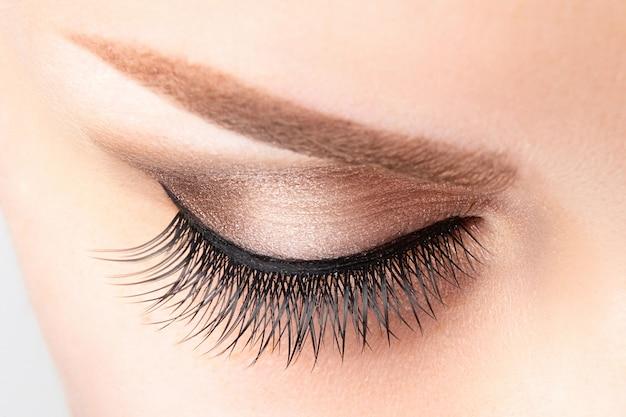 Vrouwelijk oog met lange valse wimpers, mooie make-up en lichtbruine wenkbrauwclose-up Premium Foto