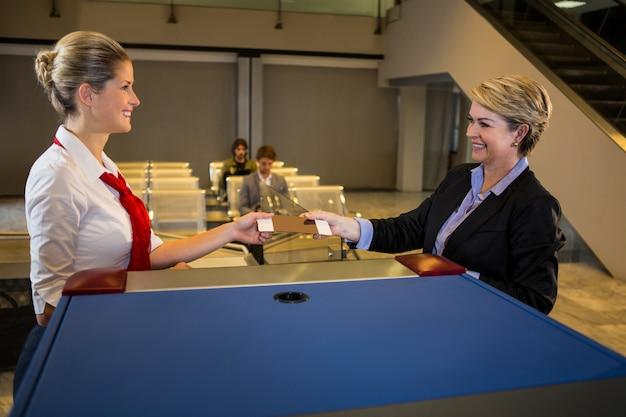 Vrouwelijk personeel dat instapkaart geeft aan de onderneemster bij teller Gratis Foto