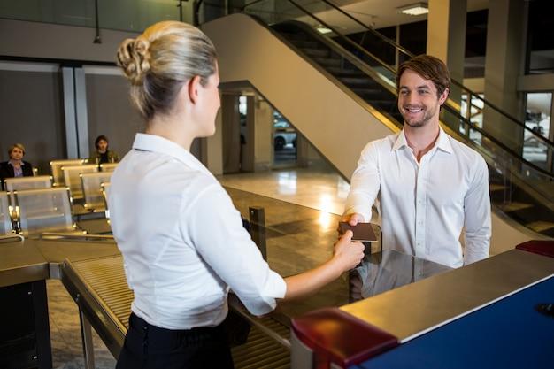 Vrouwelijk personeel dat instapkaart geeft bij de incheckbalie Gratis Foto