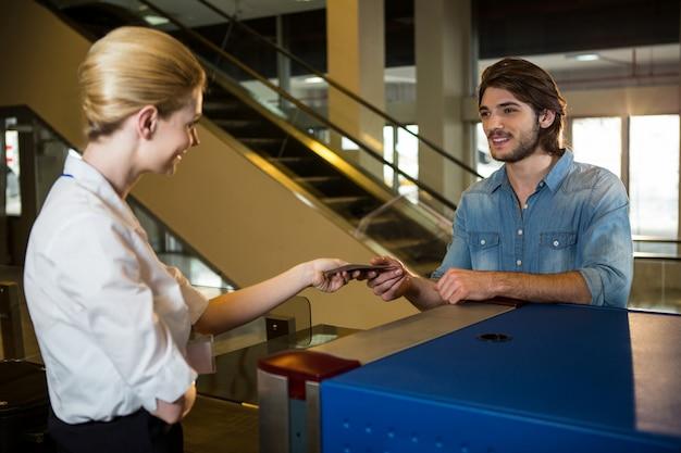 Vrouwelijk personeel geeft instapkaart aan de passagier Gratis Foto