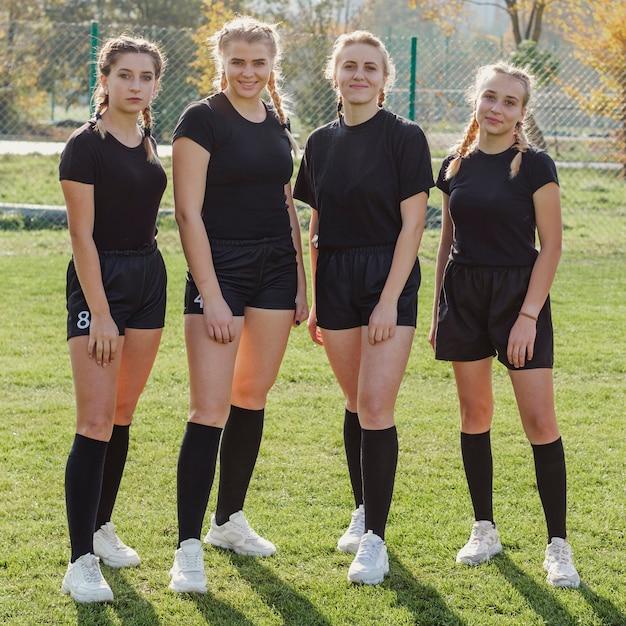 Vrouwelijk rugbyteam dat fotograaf bekijkt Gratis Foto