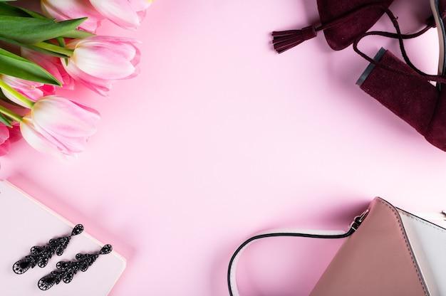Vrouwelijk thuisbureau. werkruimte met notitieboekje, roze tulp bloemen en accessoires. plat lag, bovenaanzicht. fashion blog achtergrond. mode concept. Premium Foto