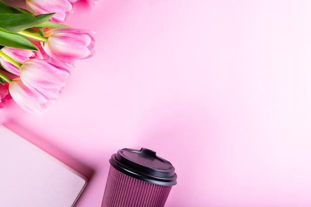 Vrouwelijk thuisbureau. werkruimte met notitieboekje, roze tulp bloemen en accessoires. plat lag, bovenaanzicht. fashion blog achtergrond. vrouwen ronduit. Premium Foto