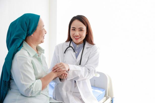 Vrouwelijke arts aanmoedigen met kanker aan de patiënt in medisch kantoor. ondersteun mensen met een tumorziekte. Premium Foto