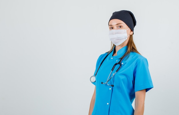 Vrouwelijke arts camera in uniform, masker kijken en zelfverzekerd kijken. vooraanzicht. Gratis Foto