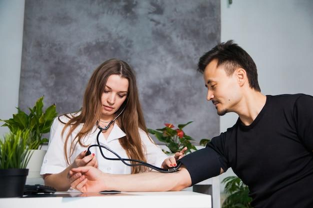 Vrouwelijke arts die arteriële bloeddruk voor patiënt op tonometer bij kliniek meet. gezondheidszorg en arts concept Premium Foto