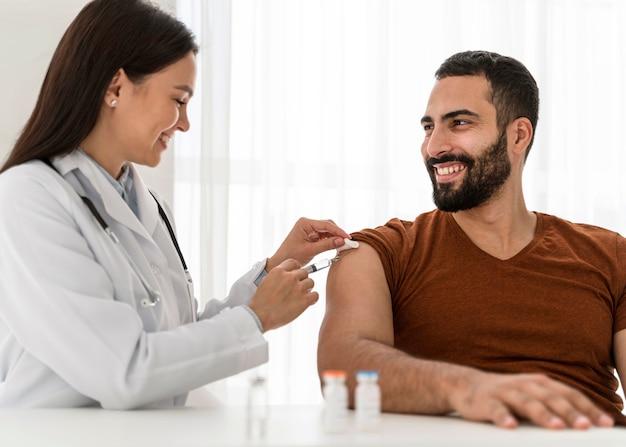Vrouwelijke arts die een knappe man vaccineert Gratis Foto
