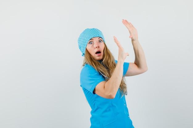 Vrouwelijke arts die palmen opheft om zich in blauw uniform te verdedigen en bang kijkt Gratis Foto
