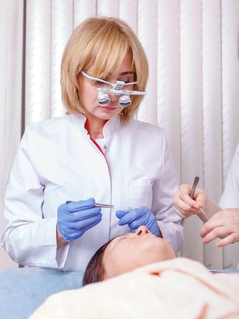 Vrouwelijke arts die persoon na plastische chirurgie onderzoekt Premium Foto